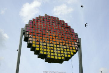 Swift tower with nest boxes for up to 100 pairs of Common swifts (Apus apus) designed as a public art work to look like a setting sun, with swifts flying overhead, Logan's Meadow Local Nature Reserve, Cambridge