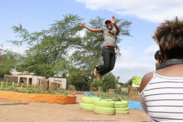 Student from Makwetse School, leaping whilst other students practice photography on Wildshots Outreach Course. Acornhoek, Mpumalanga Province, South Africa