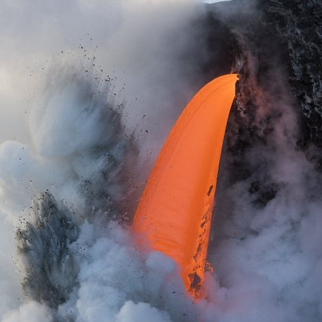 Hot lava from the 61G flow from Kilauea Volcano entering the ocean from the open end of a lava tube at the Kamokuna entry in Hawaii Volcanoes National Park, producing steam explosions, Kalapana, Puna, Hawaii. January 2017.