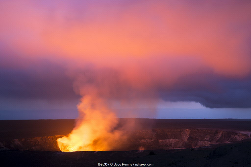 Lava lake hidden the caldera of Halemaumau Crater lights up a plume of steam, sulfur dioxide, and sulfuric acid at dusk, Kilauea Volcano, Hawaii Volcanoes National Park, Hawaii.