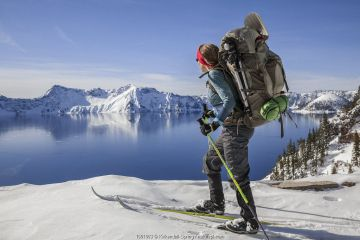 Woman cross country skiing along the north side of Rim Drive in Crater Lake National Park. Oregon, USA.