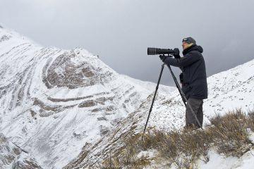 Photographer Axel Gomille, tracking and photographing snow leopards (Panthera uncia), Himalaya, Hemis National Park, Ladakh, India. February 2014.