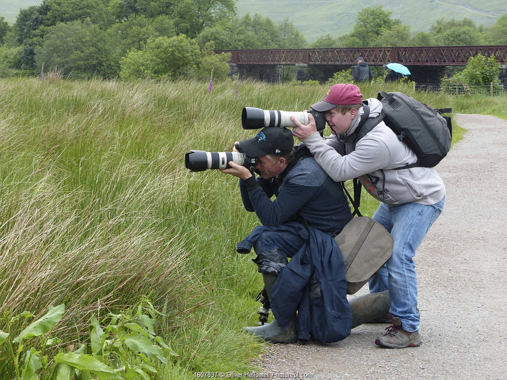 Photographer Oliver Hellowell taking pictures, balancing the camera on the head of photographer Mike O'Carroll, England, UK. June 2017.