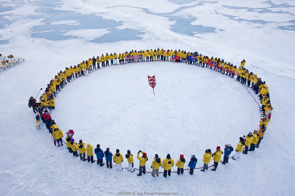 Tourists standing in a circle around the North Pole