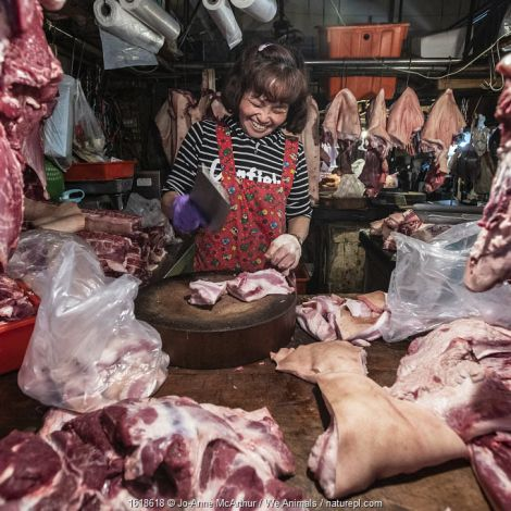 """Woman at an early-morning """"wet market"""" or produce market, carves up pig meat for sale in Taipei, Taiwan, January 2019."""