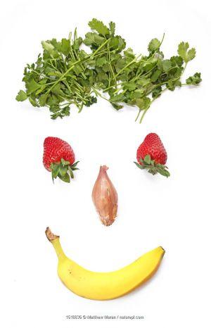 Smiling face made from parsley, strawberries, shallots and a banana.