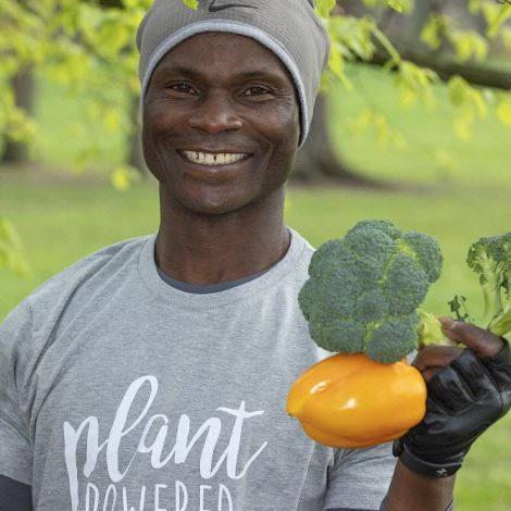 Vegan man holding broccoli and a yellow pepper, wearing a 'plant powered' t-shirt. North London, England, UK. March 2019.