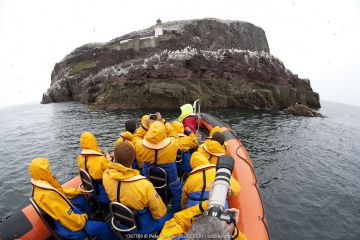 Group of tourists wearing waterproof clothing and life jackets photograph Gannet colony from zodiac boat on tour around Bass Rock, North Berwick, Firth of Forth, Lothian, Scotland, UK, August 2011. Did you know? The gannet has no nostrils, an air-sac-cushioned face and binocular vision: adaptations for effective dives on marine prey.