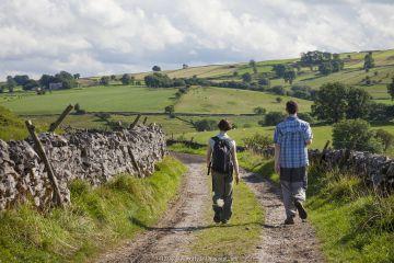 Man and woman walking along track, rear view, above Monsal Dale near Brushfield, Peak District National Park, Derbyshire, UK. August 2012