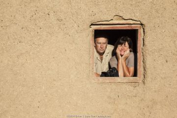 Photographers Steve and Ann Toon, looking through window in Tankwa Karoo National Park, South Africa.