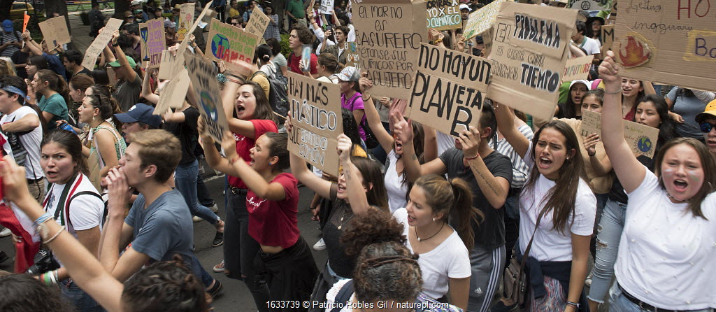 Young protestors with placards chanting during 'Fridays for the Future' climate change protest. Paseo de la Reforma Avenue, Mexico City, Mexico. September 2019.