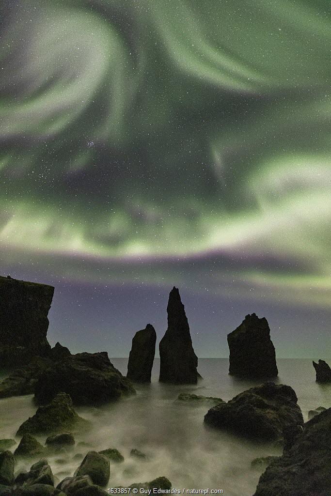 Aurora borealis over sea stacks, Reykjanes Peninsula, Iceland. 2019.