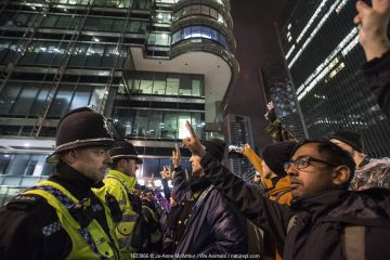 Protestors making peace sign, face to face with police officers, amongst office buildings. Extinction Rebellion climate change protest. London, England, UK. October 2019.