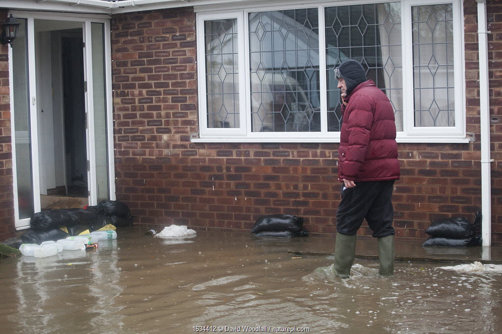 Resident walking in flooded area outside his home showing sandbags to try and keep water from entering his home, and water damage to the walls, Fishlake, South Yorkshire, UK. November 2019.