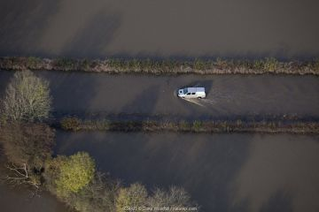Aerial view of Environment Agency vehicle driving through floodwater from River Don, Fishlake, South Yorkshire, UK. November 2019.