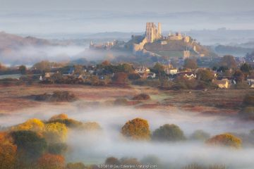 Corfe Castle in early morning mist, Dorset, England, UK, October 2018.