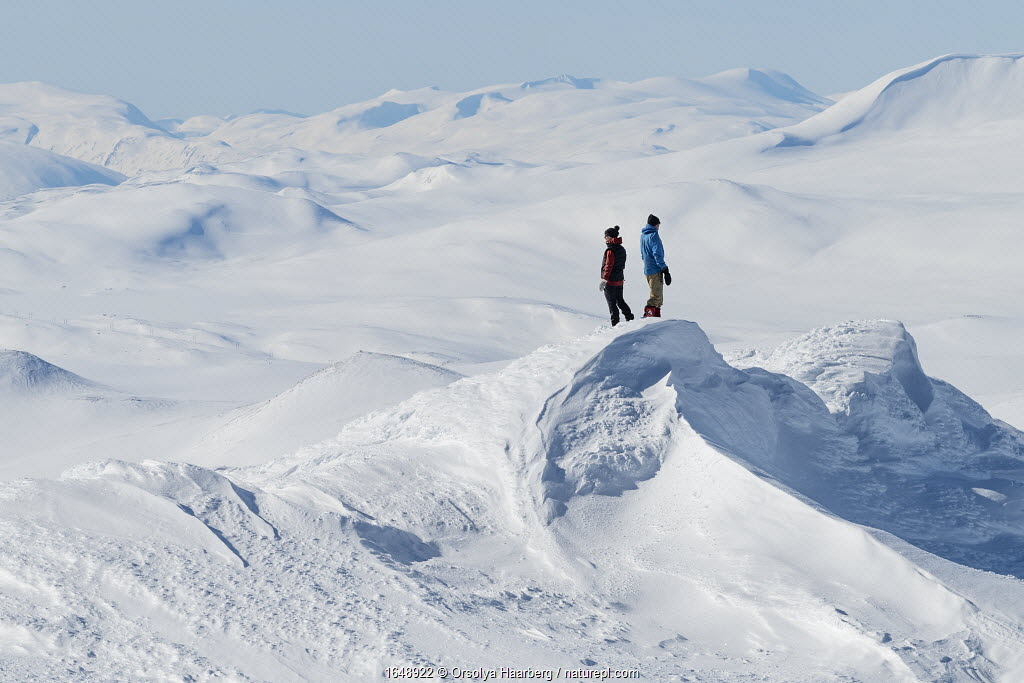 Photographers in snow-covered mountain landscape. Orsolya Haarberg and Erlend Haarberg. Vaga, Norway. March 2020.