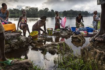 Local women washing clothes in river, Oshwe, Democratic Republic of the Congo.