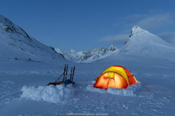 Photographers camping in the Jotunheimen mountains. Mt Kyrkja in the background. Norway. April 2020.