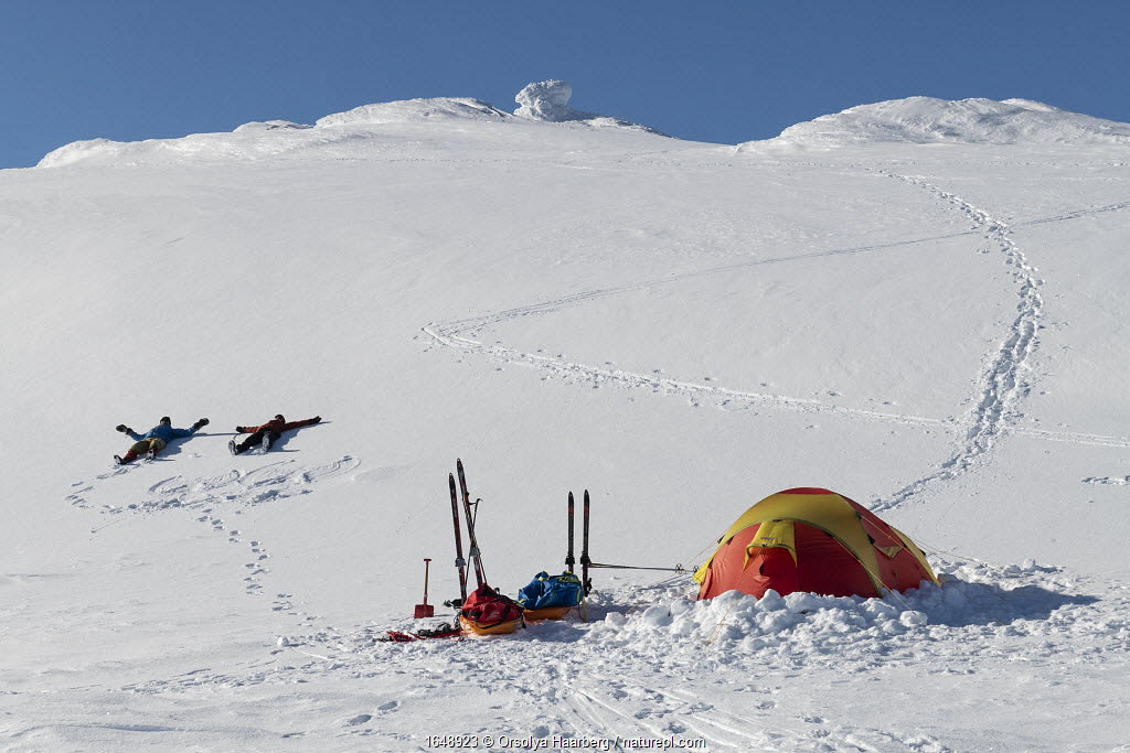 Camping on Mt Skaihoe in March. Orsolya Haarberg and Erlend Haarberg making snow angels. Vaga, Norway. March 2020.