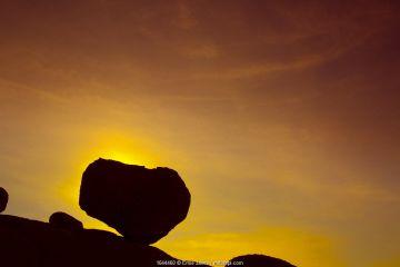 Huge boulder balanced on rocky outcrop at sunset, Namib desert, Namib-Naukluft National Park, Namibia, March