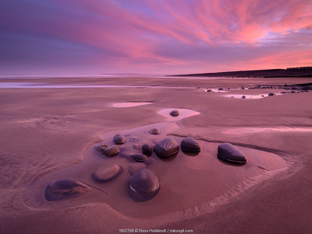 Westward Ho! beach at sunrise, colourful sky at low tide and tidal pool, north Devon, UK. February.
