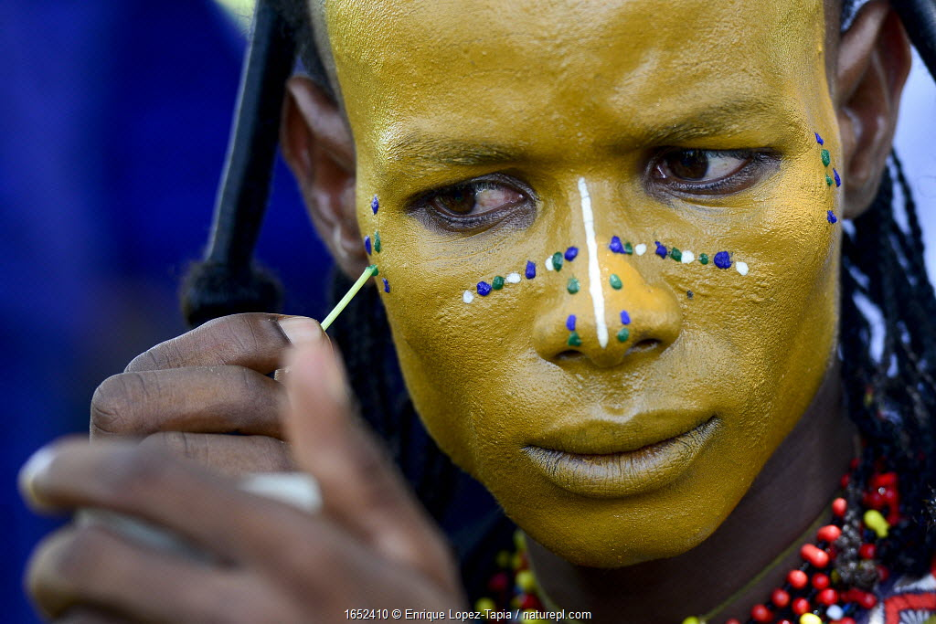 Man from Wodaabe nomadic tribe painting face for Gerewol celebration, a gathering of different clans in which women choose a husband. Men dress in best clothes and ornaments and sing and parade in front of the young women. Chad, Sahel, Africa. 2019.