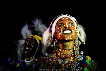 Two men from Wodaabe ethnic group dancing and singing with painted faces during Gerewol celebration, a gathering of different clans in which women choose a husband. Chad, Sahel, Africa. 2019.