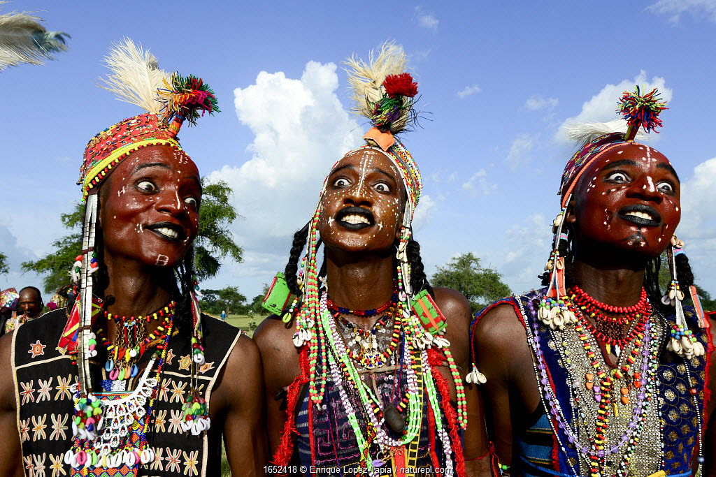 Three men from Wodaabe nomadic tribe celebrating Gerewol, a gathering of different clans in which women choose a husband. Men dress in best clothes and ornaments to sing and dance in front of the young women. Chad, Sahel, Africa. 2019.