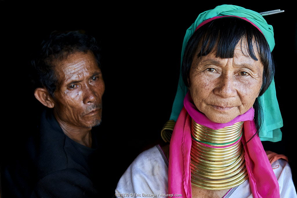 Portrait of a Kayan Lahwi woman with her husband. The Long Neck Kayan (also called Padaung in Burmese) are a sub-group of the Karen ethnic people from Burma. They wear spiral coils around their neck and lower legs.They are also nicknamed 'giraffe women'. Pan Pet Region, Kayah State, Myanmar April 2019.