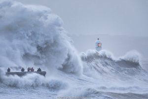 Waves crashing against sea wall and Porthcawl Lighthouse during Storm Ciara, people storm watching surrounded by waves. Mid Glamorgan, Wales, UK. February 2020.