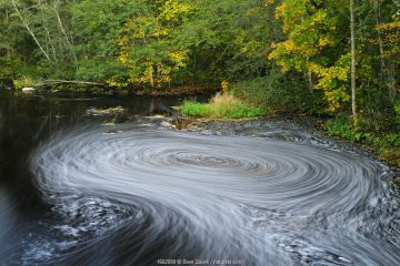 A vortex of foam and autumn leaves on Ohne river in Valgamaa county, Southern Estonia.