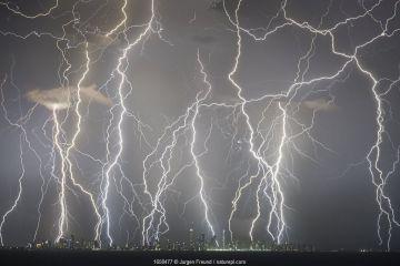 Lightning strikes above skyscrapers on Gold Coast coastline, composite image of strikes over a twenty minute period. Queensland, Australia. 2018.