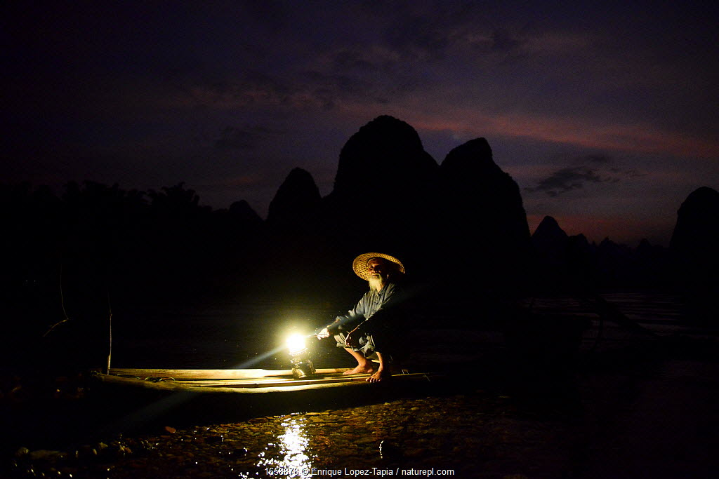 Traditional Chinese fisherman on raft on Li River at dusk, Karst peaks silhouetted in background. Yangshuo, Guangxi, China. 2016.