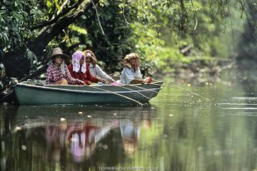 Elderly women fishing from boat on river, in rainforest. Sabah, Borneo, Malaysia.