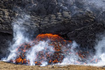 Edge of the lava field at the Fagradalsfjall volcano with a new flow of lava emerging from under the solidified lava. Fagradalsfjall, Iceland. 5 April 2021.