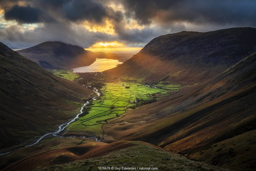 Evening sunlight illuminating Wasdale Head and Wast Water from Great Gable, Lake District National Park, Cumbria, England, UK. December 2020