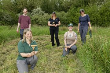Ellie Jones of Wiltshire Wildlife Trust and a team of volunteers holding their dibbers after using them to dig holes for hundreds of Devil's bit scabious (Succisa pratensis) plant plugs in a formerly farmed meadow to provide food for caterpillars of the Marsh fritillary butterfly (Euphydryas aurinia), Upper Minety Meadows reserve, Wiltshire, UK, June. Model released