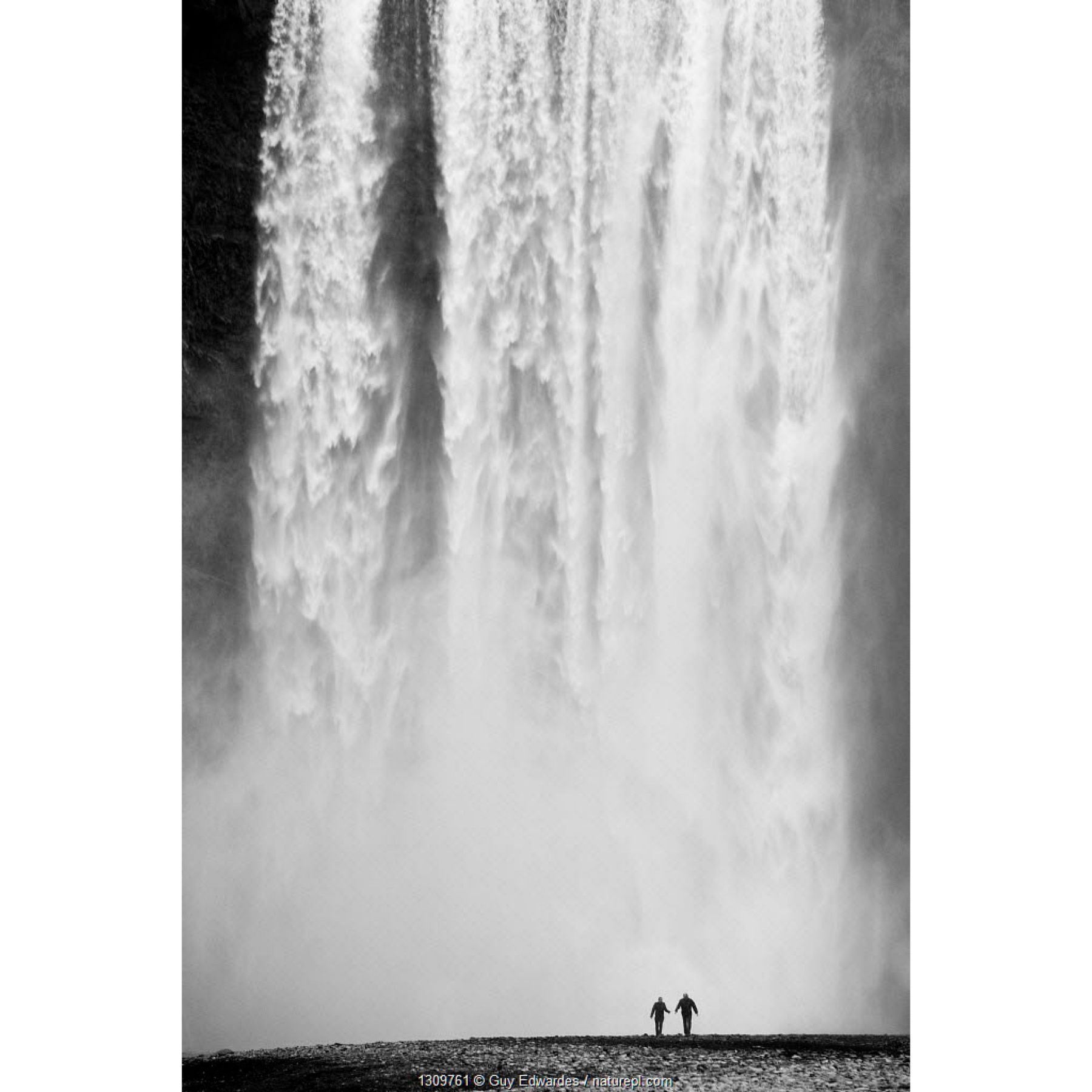 Two people silhouetted in front of Skogafoss waterfall in southern Iceland, June 2009