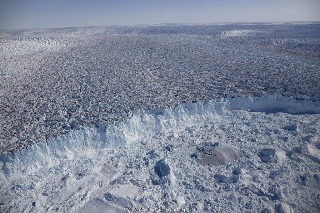 Aerial view of the front of the Sermeq Kujalleq Glacier, Greenland, entering the Kangia Ilulissat Icefjord full of icebergs. The icebergs are produced by the Sermeq Kujalleq Glacier, one of the fastest (up to 40 m a day) and most active glaciers in the world; its annual calving is over 46 km3 of ice, 10% of all Greenland calf ice