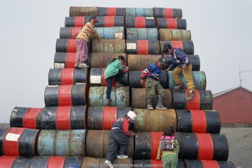 Inuit children playing on pile of empty oil drums. Moriussaq, Northwest Greenland, 1997.