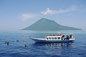 Nusantara Dive Center boat anchored at Bunaken Island dive site with Manado Tua Volcano in the distance, Manado, North Sulawesi, Indonesia - Fred Bavendam