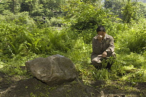 Giant Panda (Ailuropoda melanoleuca) keeper, He Changgui tearfully praying beside Mao Mao's tombstone after the May 12, 2008 earthquake and landslides, CCRCGP, Wolong, China  -  Katherine Feng