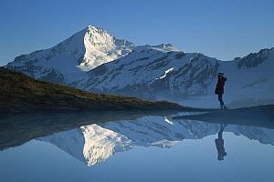 Mt Aspiring and hiker reflected in lake at dawn, Cascade Saddle, Mt Aspiring National Park, New Zealand - Colin Monteath