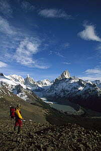 Hiker on Loma Plieque Tumbado admiring the view of Cerro Torre, left, and Fitzroy, Los Glaciares National Park, Patagonia, Argentina  -  Colin Monteath