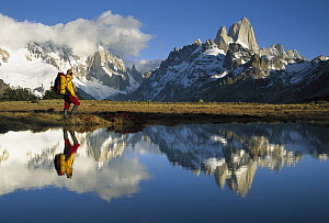 Hiker, Cerro Torre and Fitzroy reflected in small pond at dawn, Loma Plieque Tumbado, Los Glaciares National Park, Patagonia, Argentina - Colin Monteath