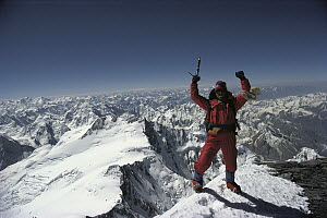 Climber on the summit of Pik Kommunizma at 7,500 meters elevation, highest mountain in the Pamirs, a mountain range in Tajikistan, central Asia - Colin Monteath