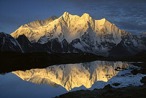 Mt Makalu (8,462 meters) and Mt Chomolonzo (7,540 meters) bathed in dawn light, reflected in small lake, Khama Valley, Tibet  -  Colin Monteath