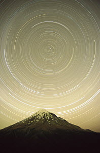 Star trails around the south celestial pole in the evening sky over the Pouakai Range, Egmont National Park, New Zealand  -  Harley Betts