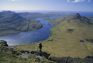 Tourist on Cul Beag looking over Loch Lurgainn and Stac Polly ridge, Scotland  -  Nick Groves
